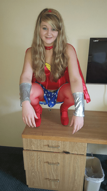 whitney sitting on a desk wearing her wonderwoman outfit